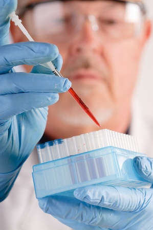 Doctor dropping blood samples into test tubes for analysis photo