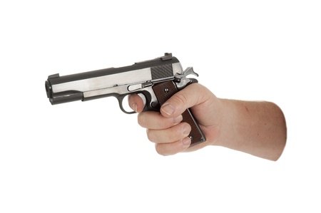 cocked: handgun cocked in a hand isolated on white