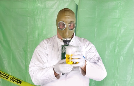 Man in Hazmat clothing in temporary green plastic decontamination chamber wearing a gas mask and carrying toxic chemical that is exuding gaseous vapor photo