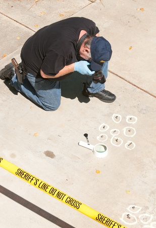 crime: Detective studying a crimes scene taking photographs  Stock Photo
