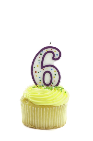 cupcake, isolated on white with a decorative candle in the shape of a number six photo