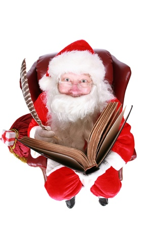 Closeup of Santa Claus (that jolly old elf that  lives at the North Pole) reading and writing in the book of good children, taken with a fish eye lens for added humor Stock Photo - 10952901