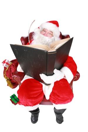 Close-up van de kerstman (dat vrolijke oude elf die leeft op de Noordpool) lezen en schrijven in het boek van de goede kinderen, genomen met een fish eye lens voor extra humor