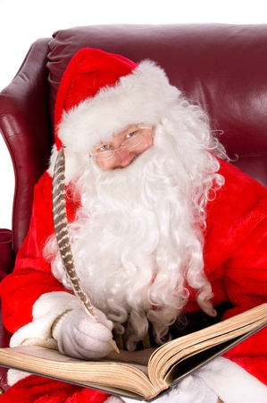 Humorus closeup of Santa Claus (that jolly old elf that  lives at the North Pole) reading and writing in the book of good children photo