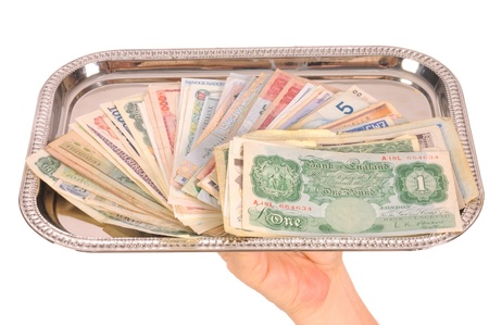 monies: Hand holding tray of world monies, isolated on white