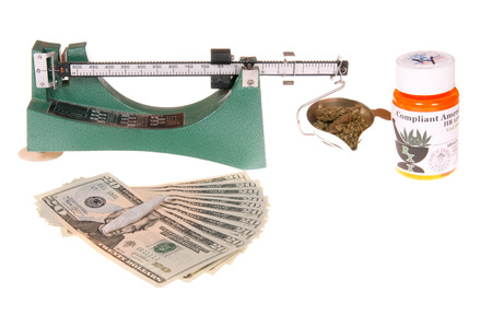 Scale for weighing marijuana with container, roll up joint and money for the transaction photo