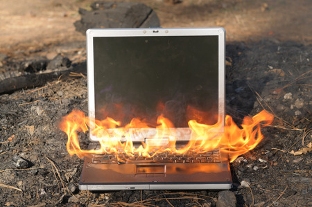 fire damage: Laptop Computer on fire Stock Photo