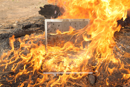 Laptop Computer setting the world on fire Stock Photo