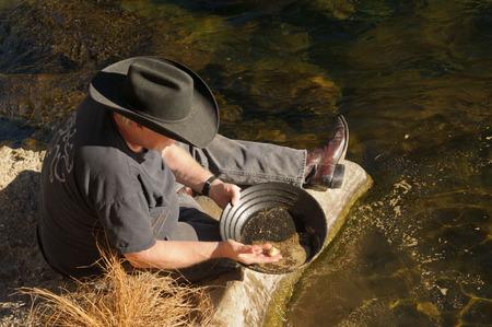 Man beside river gold panning