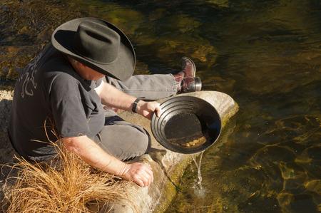 panning: Man beside river gold panning
