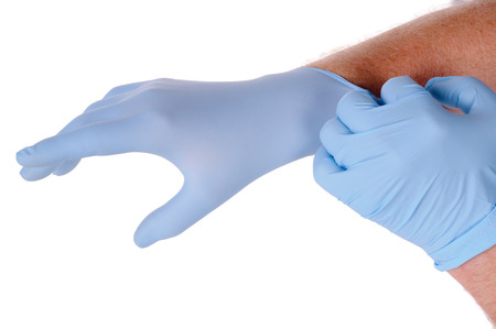 nurse gloves: close up of Doctors hands putting on nitrile gloves isolated over white