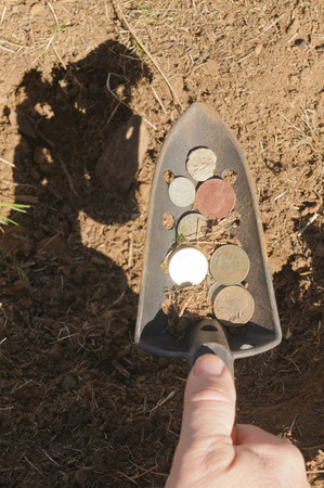 detecting: hand shovel with coins found metal detecting