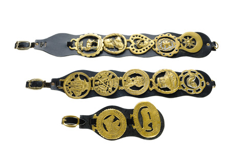 blinkers: Antique horse brasses attached to leather straps used as decoration on horses that pulled carts in the late 19th and early 20 centuries, isolated on white