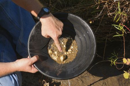 gold panning, hoping to strike it rich by finding the mother lode or at least a nugget or two 版權商用圖片 - 93611476