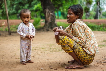 SIEM REAP, CAMBODIA - 9122015: A mother crouches next to her boy in a village.