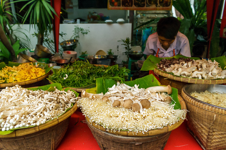 merchant: CHIANG MAI, THAILAND - 6132015: A cook prepares vegetables for food at the Sunday walking street market.
