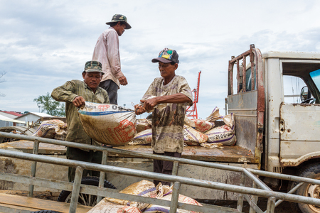 SIHANOUKVILLE, CAMBODIA - 7202015: Cambodian laborers offload bags of Ammonium Sulphate Fertilizer in a small fishing village. Editorial