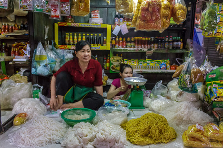 merchant: PHNOM PENH, CAMBODIA - AUGUST 11, 2015: A noodle vendor waits for customers in the Russian market in Phnom Penh. Editorial