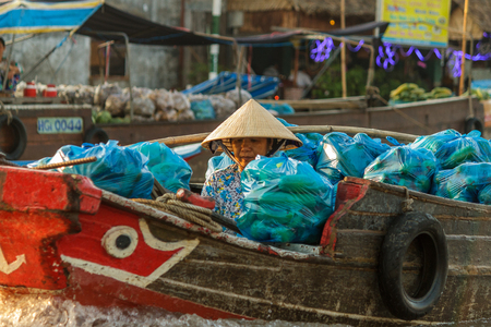 can tho: CAN THO, VIETNAM - 3242016: A merchant waits for customers at Cai Rang Floating Market on the Mekong river. Editorial