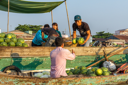 CAN THO, VIETNAM - 3242016: A merchant sells watermelon to a re-seller at Cai Rang Floating Market on the Mekong river.