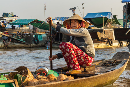 CAN THO, VIETNAM - 3242016: A coconut merchant paddles through Cai Rang Floating Market on the Mekong river to sell products to customers.