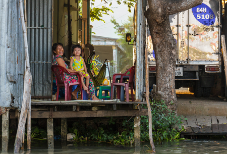 can tho: CAN THO, VIETNAM - 3242016: A woman and child at their home on the Mekong river near Cai Rang floating market in Can Tho, Vietnam.