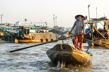 CAN THO, VIETNAM - 3242016: A merchant paddles through Cai Rang Floating Market on the Mekong river to sell products to tourists.