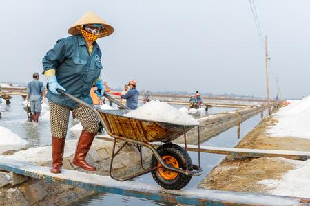 NHA TRANG, VIETNAM - 4122016: A woman pushes a wheelbarrow of salt  at the Hon Khoi salt fields in Nha Trang, Vietnam. Editöryel