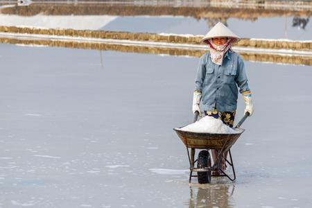 hon: NHA TRANG, VIETNAM - 4122016: A woman pushing a wheelbarrow of salt at the Hon Khoi salt fields in Nha Trang, Vietnam.