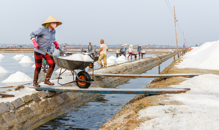 hon: NHA TRANG, VIETNAM - 4122016: A woman works at the Hon Khoi salt fields in Nha Trang, Vietnam.