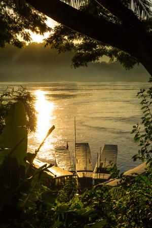 Tour boats at sunrise on the Mekong River in Luang Prabang, Laos