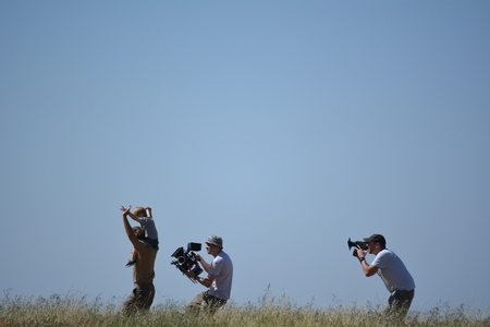 Movie set father and son run through grass camera men follow Editorial