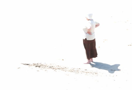 Isolated view of woman on beach staring into distance