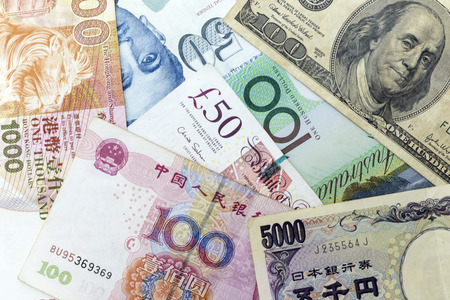 Currency banknotes spread across frame including world major currencies