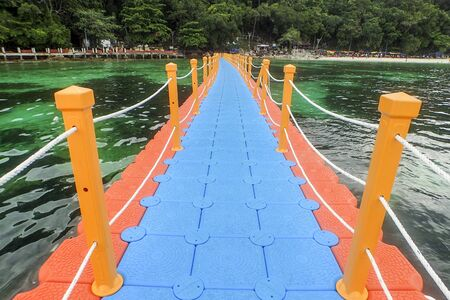 Colorful pontoon floating on seashore connecting boats landing to the beach