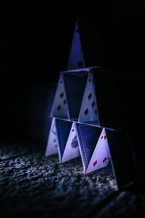 Flimsy pile of playing cards stacked in seemingly stable house of cards
