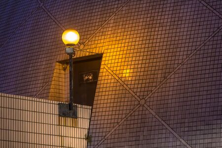 Mosiac style wall illuminated by street lighting in tungsten color