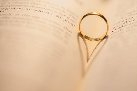 Warm light cast golden ring shadow on open book with shallow depth of field