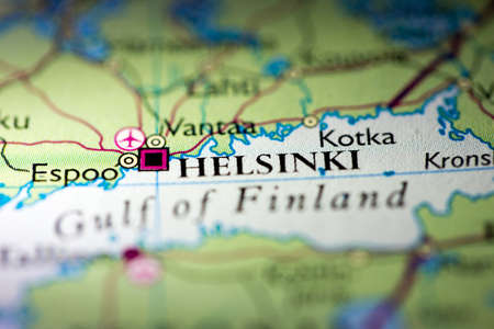 Shallow depth of field focus on geographical map location of Helsinki city Poland Europe continent on atlas