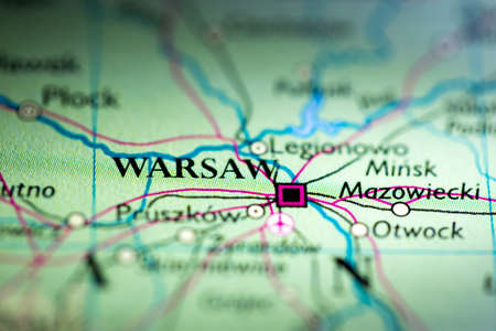 Shallow depth of field focus on geographical map location of Warsaw city Poland Europe continent on atlas