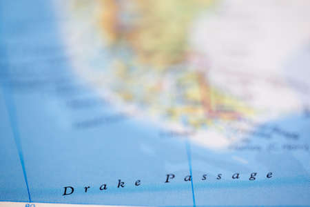 Shallow depth of field focus on geographical map location of Drake Passage off coast of Argentina on atlas