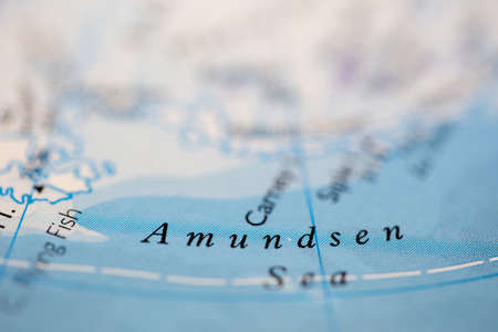 Shallow depth of field focus on geographical map location of Amundsen Sea off coast of Antarctica on atlas