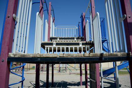 Playground wood climbing area in school yard with school in background. Stock Photo