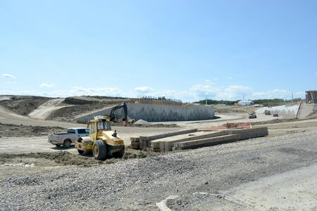 Highway construction site with concrete and steel reinforcement and equipment.