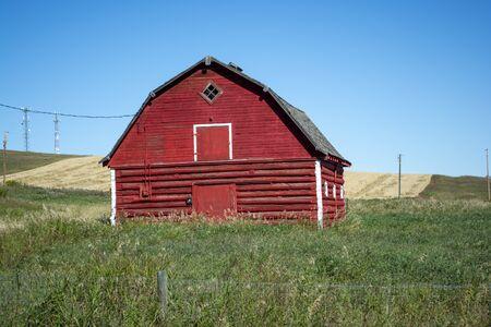 Old Red Barn on Grassy Farmland Prairie Imagens