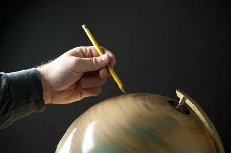 A hand holding a pencil and pointing at a spinning globe.