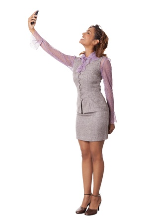 hour glass figure: Cute business woman takes a self portrait with her cell phone, isolated on white background  Stock Photo