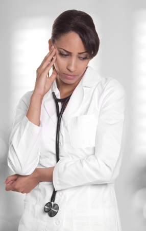 Female doctor in white is upset and lost in thought