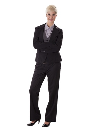 Businesswoman in a pant suit stands smiling with arms crossed  Stock fotó