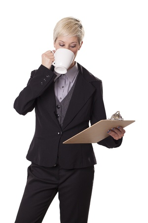 Attractive, young woman sips from a coffee cup while looking at a clipboard